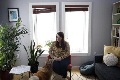 Lisa Quinn and her dog Anya live in her energy-efficient Medford condo, which has a special system to control the temperature and solar panels on the roof of its building.